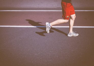 man-running-on-concrete-road-in-sun
